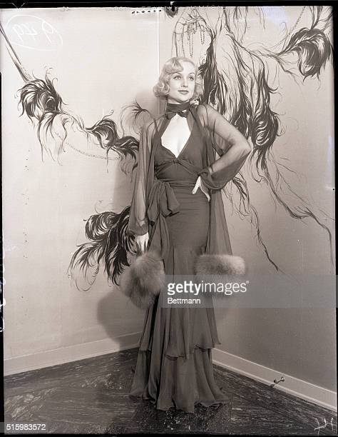 6/28/1933 picture shows actress Carole Lombard posing in an elaborate chiffon gown with a fur trim and a open vneck
