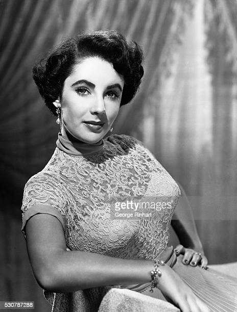 Picture shows actress Elizabeth Taylor posing in a dress with a lace embroidered top with a pleated chiffon bottom Undated photo circa early 1950s