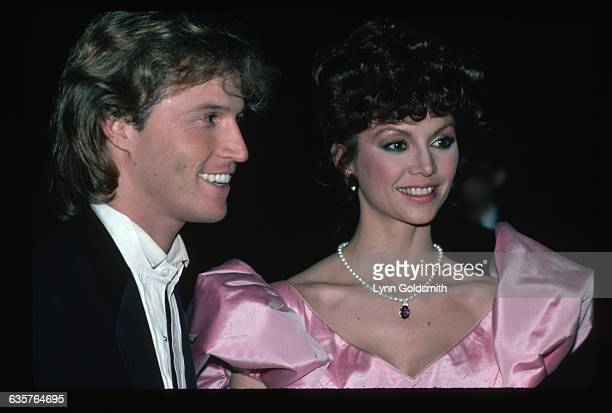 1982 Picture shows actress Victoria Principal and singer Andy Gibb posing together She is shown in a pink satin dress and a pearl necklace He is in a...