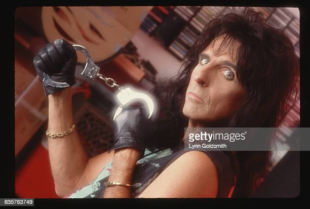 1989 Picture shows Alice Cooper posing inside with a pair of handcuffs He is shown from the shoulders up and is looking into the camera He is wearing...