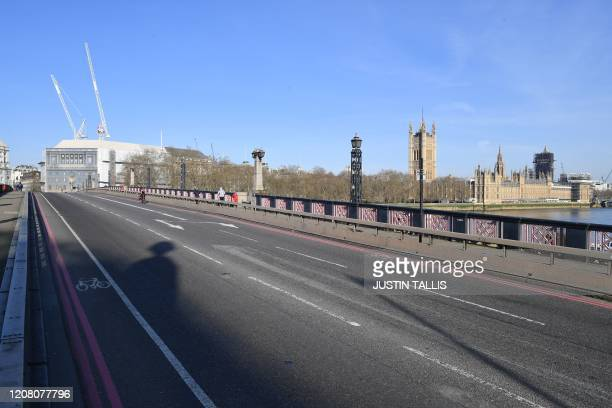 A picture shows an empty Lambeth Bridge with the Houses of Parliament in the background in central London in the morning on March 24 2020 after...