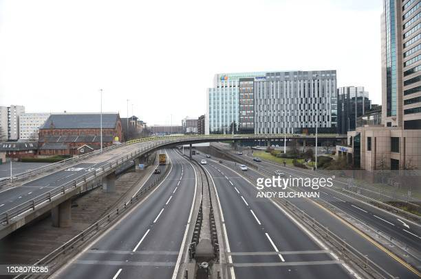 A picture shows an empty M8 motorway in the centre of Glasgow during what would normally be the busy morning rush hour on March 24 2020 after Britain...