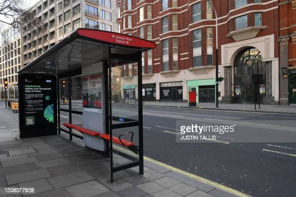 A picture shows an empty street and bus stop at St James's Park in central London in the morning on March 24 2020 after Britain ordered a lockdown to...