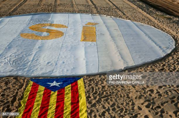 Picture shows an Estelada beside a banner reading SI on El Masnou beach near Barcelona on September 3 during an action called by ANC to support a...