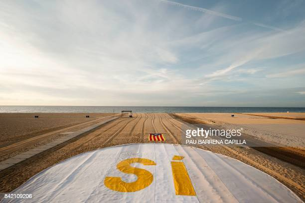 Picture shows an 'Estelada' beside a banner reading 'SI' on El Masnou beach near Barcelona on September 3 during an action called by ANC to support a...