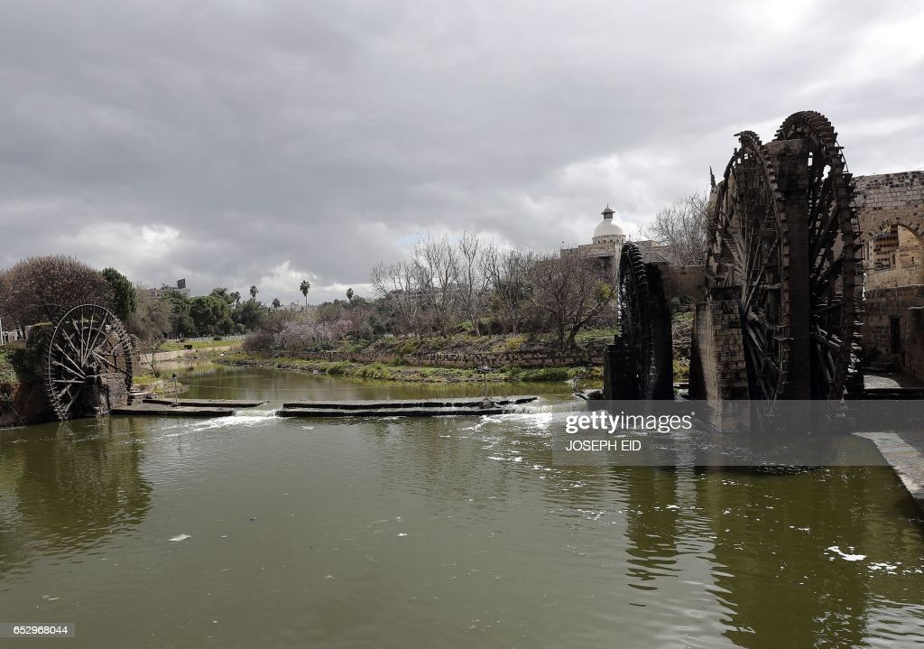 A picture shows ancient water wheels, or norias, along the Orontes River in Hama in central Syria, on March 13, 2017. /
