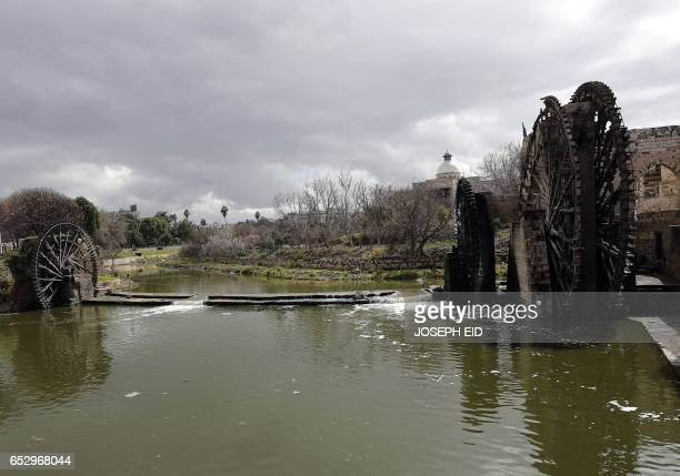 A picture shows ancient water wheels or norias along the Orontes River in Hama in central Syria on March 13 2017 / AFP PHOTO / JOSEPH EID