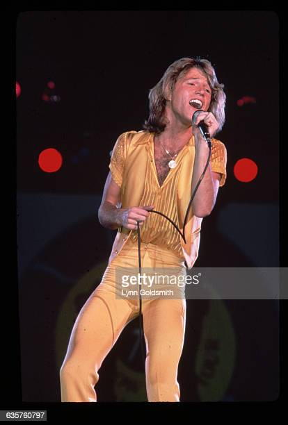 1978 Picture shows Andy Gibb singing in concert He is holding a microphone and wearing tight yellow pants and a yellow shirt