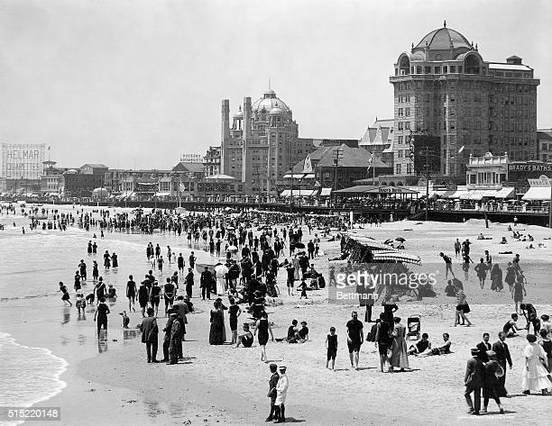 1911 Picture shows Atlantic City beach and boardwalk buildings There are people on the beach in business suits as well as bathing suits