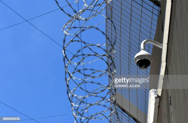 A picture shows barbwire video camera and cells over the excercice yard in the Sante prison in Paris on June 28 2018 Closed since 2014 for renovation...