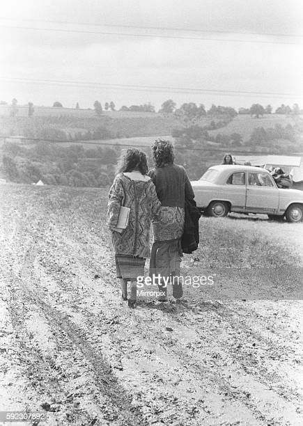 Bare footed hippie couple walking through muddy fields at the festival 19th June 1971