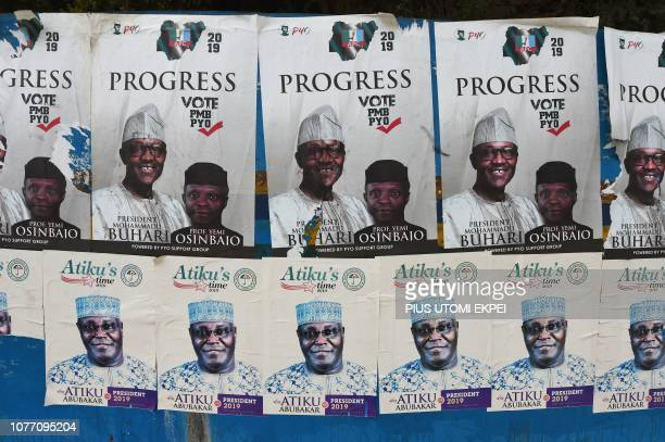 A picture shows campaign posters for Nigeria's incumbent president and candidate to his reelection for the ruling All Progressives Congress President...