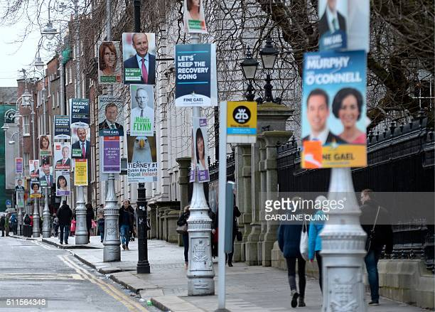 A picture shows campaign posters for the parliamentary elections on lamposts outside Government Buildings in Dublin Ireland on February 21 2016 Polls...