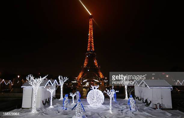 A picture shows Christmas decorations in front of the Eiffel tower on December 13 in Paris as part of the 'Trocadero On Ice' event An iceskating rink...