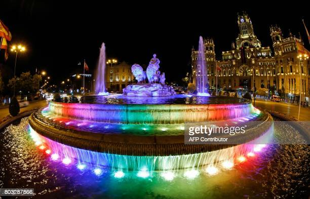 Picture shows Cibeles fountain illuminated with the rainbow colours in Madrid on June 28 2017 Thousands of revellers many draped in rainbow flags...