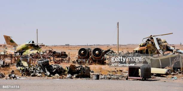 A picture shows destroyed fighter jets and a helicopter at the military airport in the eastern Syrian city of Deir Ezzor on September 11 as Syrian...