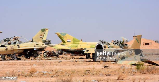 A picture shows destroyed fighter jets at the military airport in the eastern Syrian city of Deir Ezzor on September 11 as Syrian government forces...