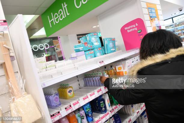 A picture shows empty shelves where antibacterial hand sanitiser gels have sold out in a drug store in London on March 3 2020 Up to one fifth of...