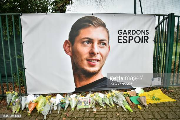 TOPSHOT A picture shows flowers layed under a portrait of Argentinian forward Emiliano Sala prior to a team training session at the FC Nantes...