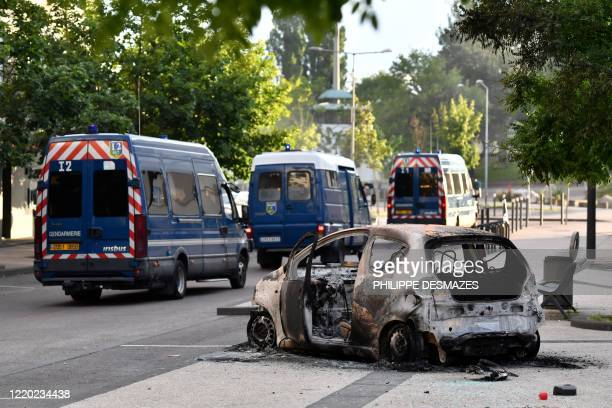 Picture shows gendarmes can on a road near a burnt car in the Gresilles area of Dijon, eastern France, on June 15 as new tensions flared in the city...