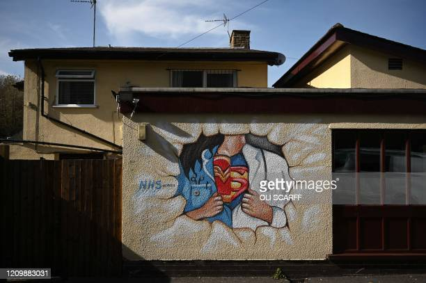 TOPSHOT A picture shows graffiti depicting the badge of a superhero under a nurse's and doctor's uniform in homage to the efforts of NHS staff during...