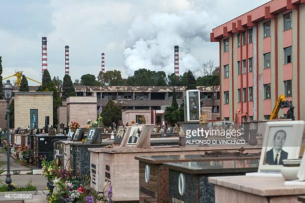 IDE A picture shows graves in the cemetery of Taranto with the Ilva steel plant in the background on March 18 2015 The site in Taranto in the Puglia...
