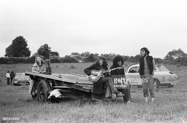 Group of friends sitting on the back of a trailer playing guitar and singing songs at the festival 19th June 1971