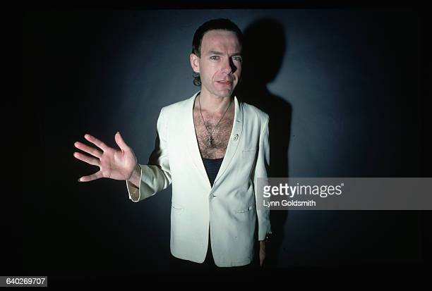 1981 Picture shows guitar player Robert Fripp of the band King Crimson posing in a white jacket and low cut black tank top One hand is extended...