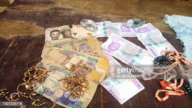 A picture shows jewellery items and banknotes recovered from suspected Boko Haram militants displayed by the police in Maiduguri northeast Nigeria on...