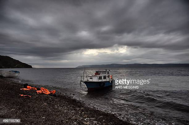 A picture shows life jackets left on the beach after a group of refugees and migrants arrived on the Greek island of Lesbos on December 3 after...