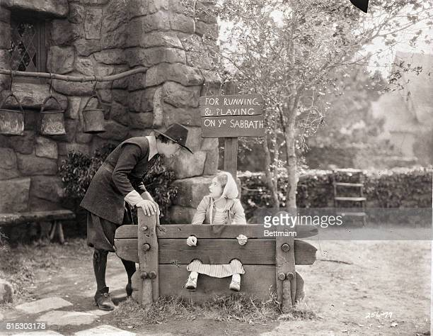 1926 Picture shows Lillian Gish sitting in stocks while Lars Hanson chats to her Movie still from THE