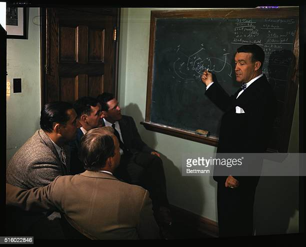 Picture shows Notre Dame football coach Frank Leahy and players studying plays for a game