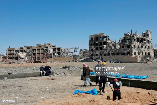 Picture shows on April 23, 2018 Syrians recovering bodies that have been found in a mass grave in the former Islamic State group stronghold of Raqa...