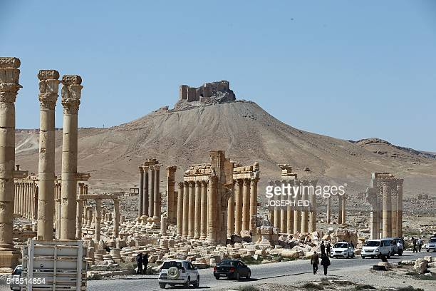A picture shows on March 31 2016 people walking near the remains of Arch of Triumph also called the Monumental Arch of Palmyra in the ancient Syrian...