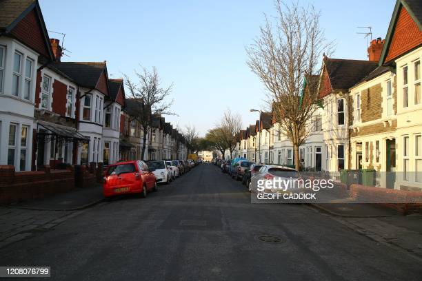 Picture shows parked cars and streets empty of pedestrians in Cardiff, South Wales, in the morning on March 24, 2020 after Britain ordered a lockdown...