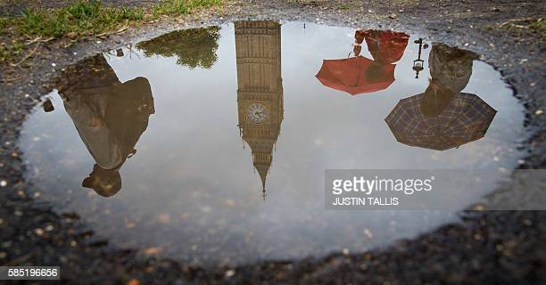 A picture shows people reflected in a puddle as they walk past Elizabeth Tower at the Houses of Parliament during a rain shower in London on August 2...