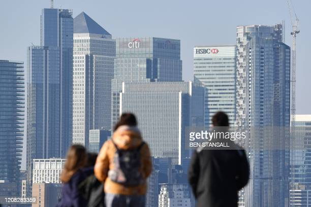 A picture shows people standing at the look out toward the financial towers and bank offices of Canary Wharf from Greenwich Park in London on March...