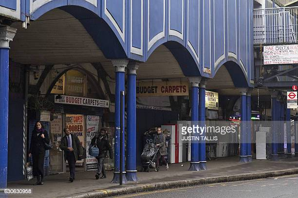A picture shows people walking past commercial units in the viaduct arches near to Brixton railway station in south London on December 19 2016 Local...