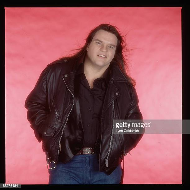 Picture shows performer Meatloaf posing in front of a red background weaing a leather jacket and jeans with a smirk on his face