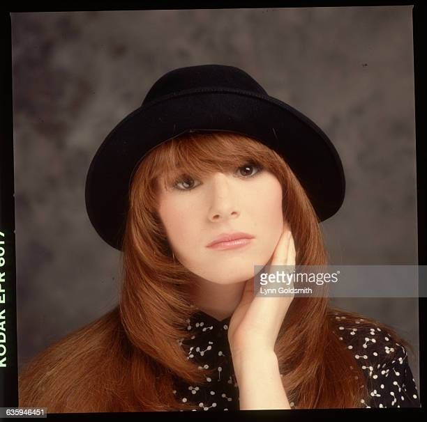 Picture shows pop singer, Tiffany, wearing a black hat and her hand placed on her cheek.