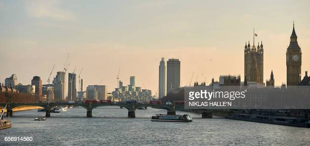 A picture shows red London buses pedestrians and traffic crossing Westminster Bridge over the River Thames with the Union flag atop the Houses of...