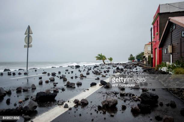 TOPSHOT A picture shows rocks swept by strong waves onto a road in Le Carbet on the French Caribbean island of Martinique after it was hit by...