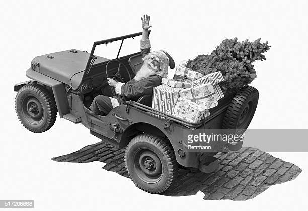 Picture shows Santa Claus in a jeep with a Christmas tree and presents Undated photo circa 1942