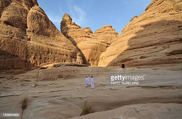 A picture shows Saudi men walking at a carved rosecoloured sandstone mountain in the Nabataean archaeological site of alHijr near the northwestern...
