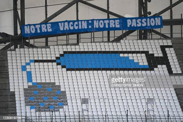 """Picture shows seats fitted with coloured sheets to depict a syringe and the Covid-19 coronavirus and a banner reading """"Our Vaccine: Our passion"""" in..."""