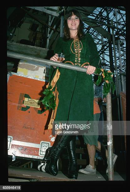 Picture shows singer and musician Ann Wilson posing backstage at a concert wearing a green suede outfit with black platform boots and holding on to a...
