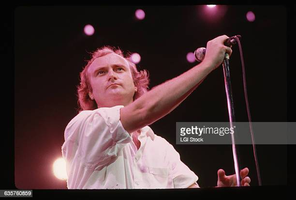 1987 Picture shows singer Phil Collins holding a microphone on stage during a concert He is wearing a white buttondown with the sleeves rolled up to...