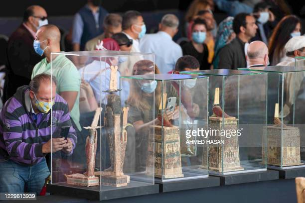 A picture shows statues and funerary masks on display during the unveiling of an ancient treasure trove of more than a 100 intact sarcophagi at the...