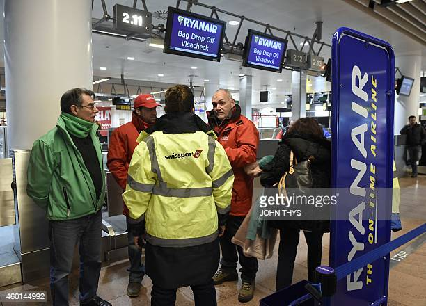 A picture shows strikers staying at the Raynair checkin desk at Brussels airport on December 8 as part of a strike called by several unions to...