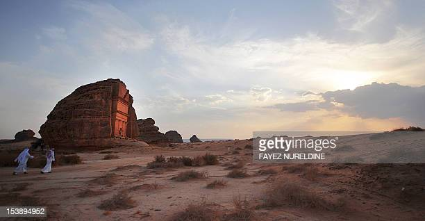 A picture shows Sudi men walking near a carved rosecoloured sandstone mountain in the Nabataean archaeological site of alHijr near the northwestern...